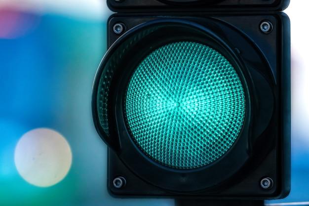Close-up van verkeersseinpaal met groen licht op defocused stadsstraatachtergrond met exemplaarruimte