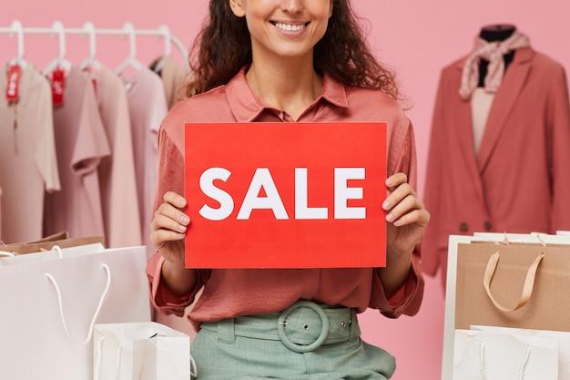 Close-up van verkoopster verkoop aanplakbiljet houden en glimlachen tijdens het werken in de winkel