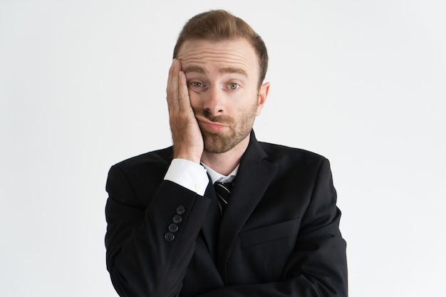 Close-up van vermoeide en verveelde bedrijfsleider. bebaarde jonge blanke man in gelijkspel en jas