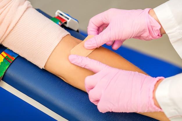 Close up van verpleegkundige hand zelfklevende pleister toe te passen op de arm van de patiënt na de bloedafname in het ziekenhuis