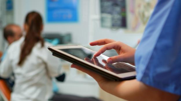 Close-up van verpleegster die vasthoudt en typt op een tablet die in de stomatologische kliniek staat, terwijl de arts met de patiënt op de achtergrond werkt. monitor gebruiken met chroma key izolated pc-sleutel mockup pc-display