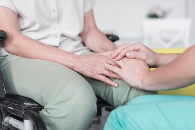 Close-up van verpleegster en patiënt die elkaars hand houden