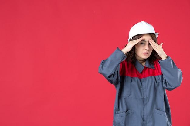 Close-up van verrast geschokt vrouwelijke bouwer in uniform met harde hoed op geïsoleerde rode muur