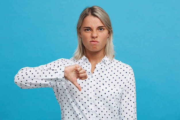 Close-up van verrast opgewonden blonde jonge vrouw met geopende mond draagt polka dot-shirt voelt zich gelukkig, raakt haar gezicht aan en kijkt verbaasd geïsoleerd over blauwe muur