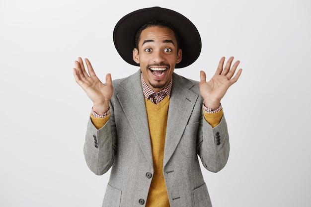 Close-up van verrast vrolijke afro-amerikaanse man verheugt zich van geweldig nieuws, klappen in de handen, feliciteren met winnen