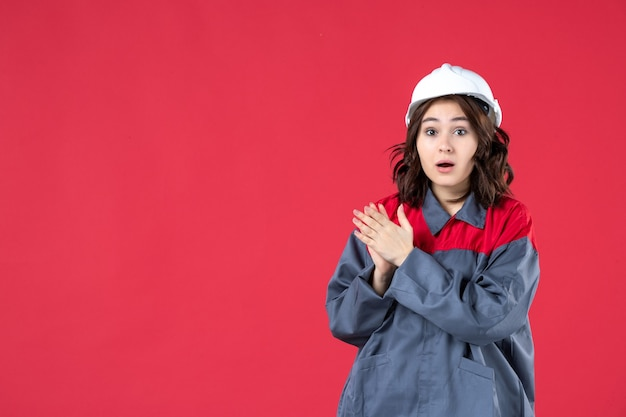 Close-up van verrast vrouwelijke bouwer in uniform met harde hoed en applaus voor iemand op geïsoleerde rode muur