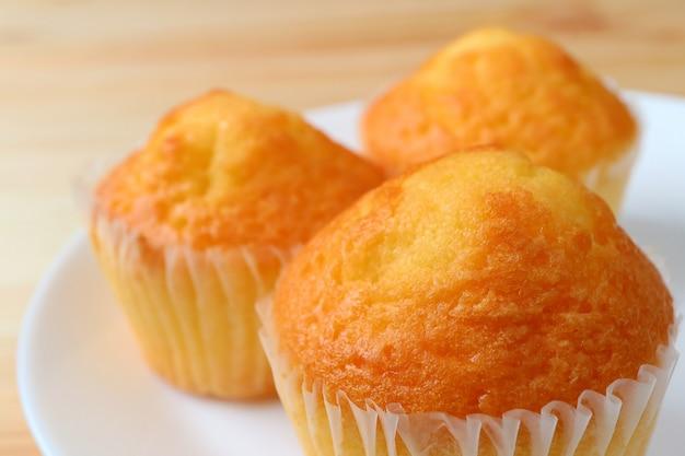 Close-up van verrukkelijke madeleine cupcakes geserveerd op witte plaat, selectieve aandacht