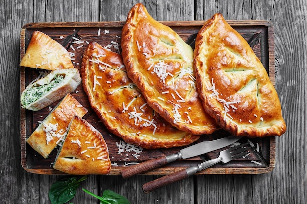 Close-up van vers gebakken calzones, gesloten pizza's met spinazie en kaasvulling bestrooid met geraspte parmezaanse kaas op een onbeleefde houten plank op een rustieke houten tafel, italiaanse keuken, flatlay