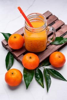 Close-up van vers mandarijnensap in een glazen pot met een herbruikbaar plastic rietje op een houten dienblad