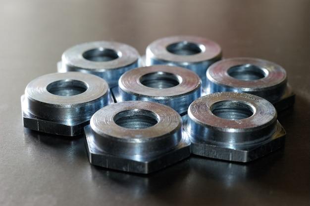Close-up van verschillende platte metalen moeren liggend op een metalen oppervlak in een werkplaats