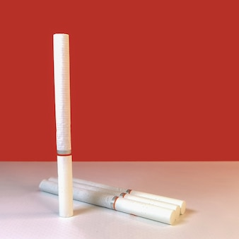Close-up van verschillende sigaretten met een wit filter liggend op een tafel op een wit bureau.