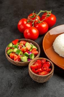 Close-up van verschillende soorten groenten en rijst op een bruine plaat op donker