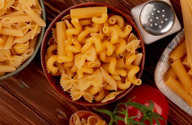 Close-up van verschillende soorten macaroni in kommen en zout tomaat op houten oppervlak