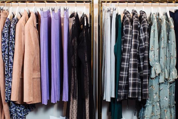 Close-up van verschillende stijlvolle kleding hangers in boetiek hangen. kleren