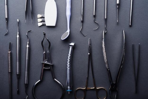 Close-up van verschillende tandheelkundige instrumenten samengesteld op grijze achtergrond