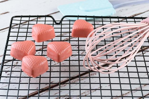 Close-up van verschillende witte chocolaatjes getint met roze verf, op een zwart hek, naast een spatel en een fouet.