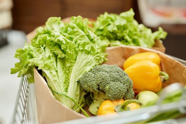 Close-up van verse biologische groenten en fruit in papieren zak gestapeld in winkelwagen in supermarkt, gezonde voeding en kruidenier shopping concept