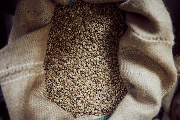 Close up van verse bonen van arabica koffieplant opgeslagen in zak