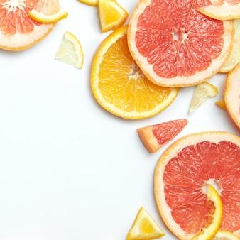 Close-up van verse citrusvruchten citroen, sinaasappel en grapefruit plakjes op wit oppervlak