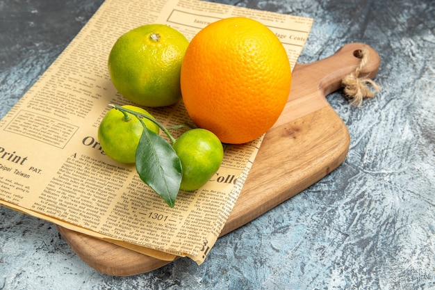 Close-up van verse citrusvruchten met bladeren en krant op houten snijplank, in halve vormen gesneden grijze tafel