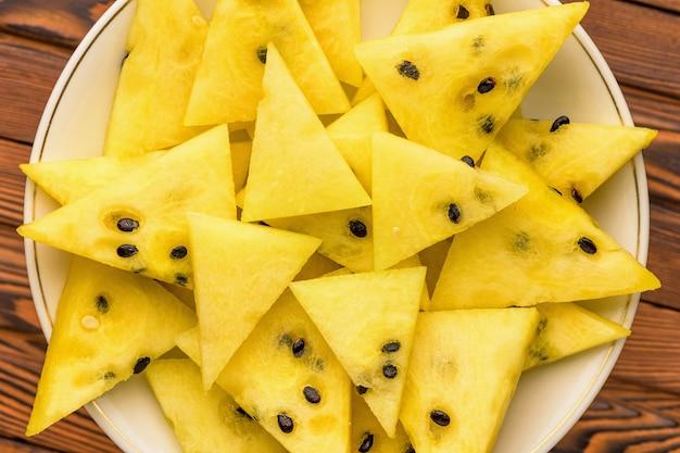 Close-up van verse gele watermeloenplakken op witte plaat