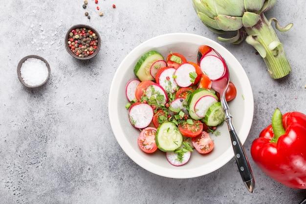 Close-up van verse gezonde salade in een kom gemaakt van tomaten, komkommer, radijs en kruiden, met rauwe artisjok en kruiden, goed voor dieet of detox, grijze rustieke stenen achtergrond
