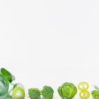 Close-up van verse groene groenten op witte oppervlakte