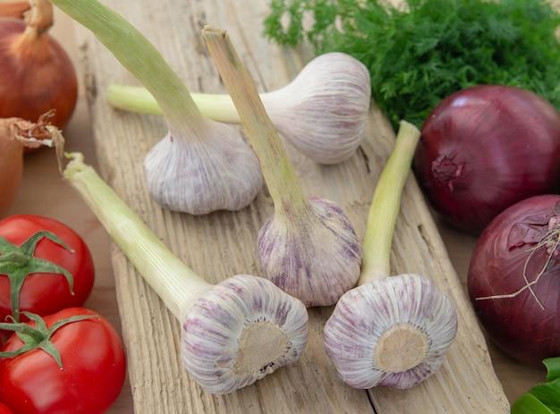 Close-up van verse groenten (tomaten, uien, radijsjes, gras, knoflook) op een houten bord.