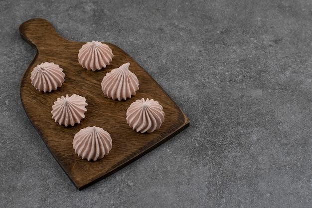 Close up van verse meringues op houten snijplank