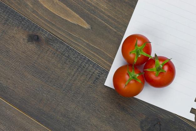 Close-up van verse, rijpe tomaten met witboek op houten lijst