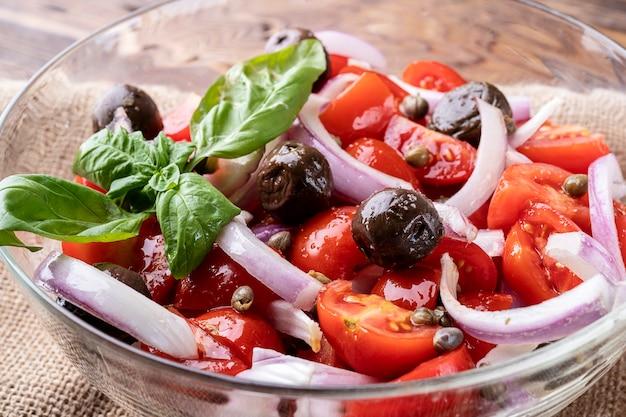 Close up van verse salade met cherrytomaat, olijven, onionnasil en kruiden dieet voedsel concept