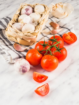 Close-up van verse, sappige tomaten; uien; knoflookteentjes en doek op marmeren achtergrond