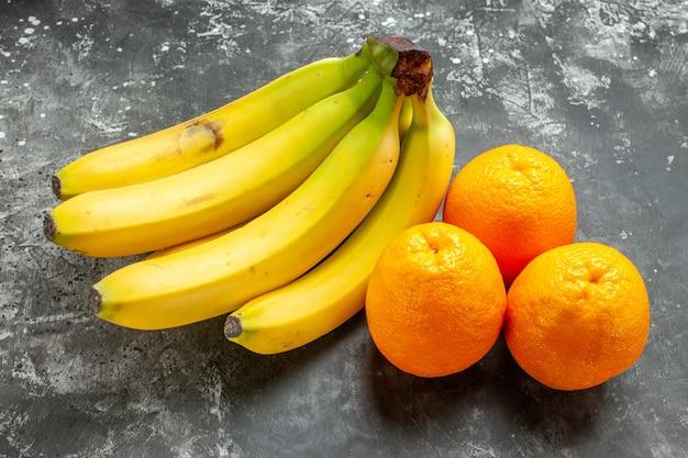 Close-up van verse sinaasappels en natuurlijke biologische bananen bundel donkere achtergrond