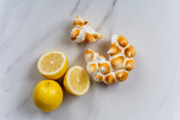 Close-up van verse zelfgemaakte citroentaart met meringue en citroencitrusvruchten. bakkerij concept.