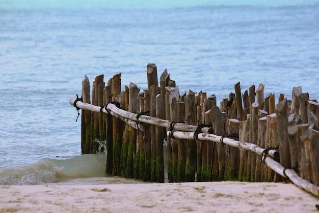 Close-up van verticale houten planken van een onafgewerkt dok op het strand, omringd door de zee