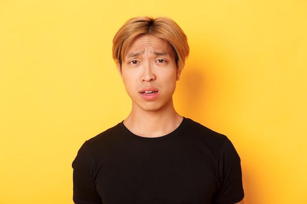 Close-up van verwarde en verstoorde aziatische blonde kerel die verbaasd, open mond en fronsend perplex kijkt, die zich over gele muur bevindt.