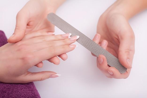 Close-up van vier vrouwelijke handen. professionele manicure die nagellak doet.