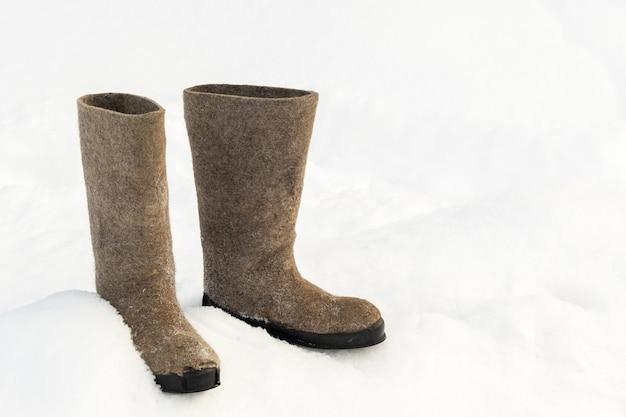 Close-up van vilten laarzen die in de sneeuw staan.
