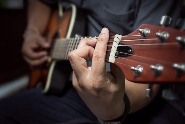 Close-up van vingers van akoestische gitaar spelen