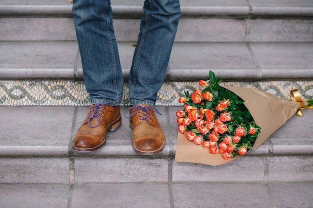 Close-up van vintage schoenen met paarse veters en een boeket rozen