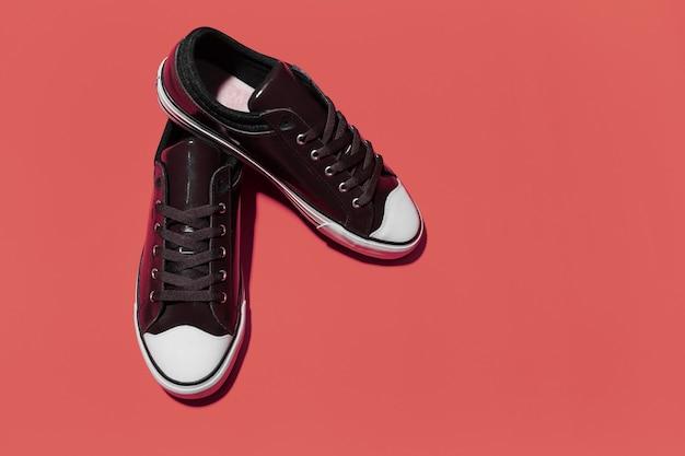 Close-up van vintage sneakers op rode achtergrond.