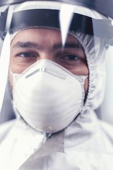 Close-up van viruswetenschapper die ppe-apparatuur draagt in het microbiologisch laboratorium tijdens covid19. overwerkte onderzoeker gekleed in beschermend pak tegen infectie met coronavirus tijdens wereldwijde epidemie.