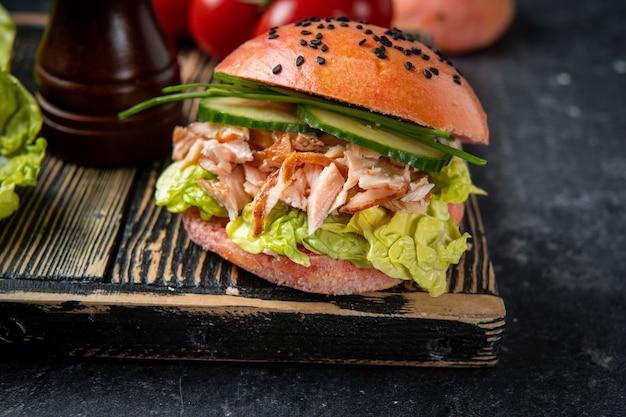 Close-up van vis hamburger met roze broodje en zalm op zwart
