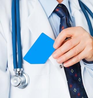 Close-up van visitekaartje in de hand van de arts, en doc. zette de kaart in de zak