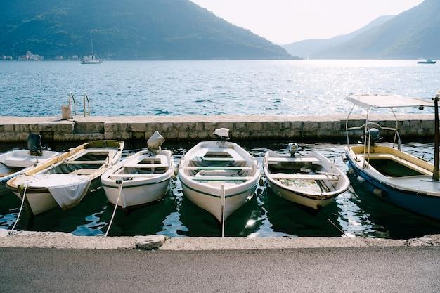 Close-up van vissersboten op de pier van de stad perast tegen de achtergrond van bergen en