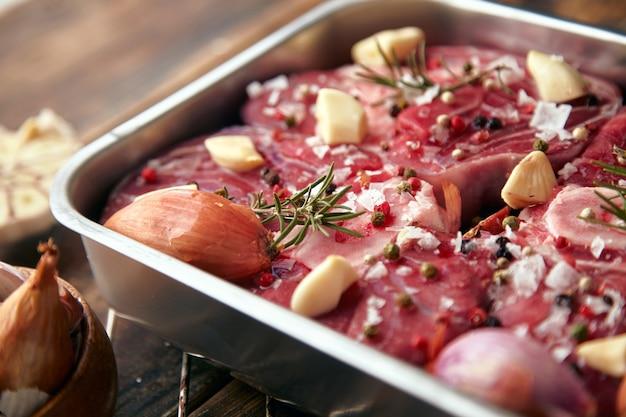Close-up van vlees in de kruiden van de staalpan rond: knoflook, rozemarijn, uien