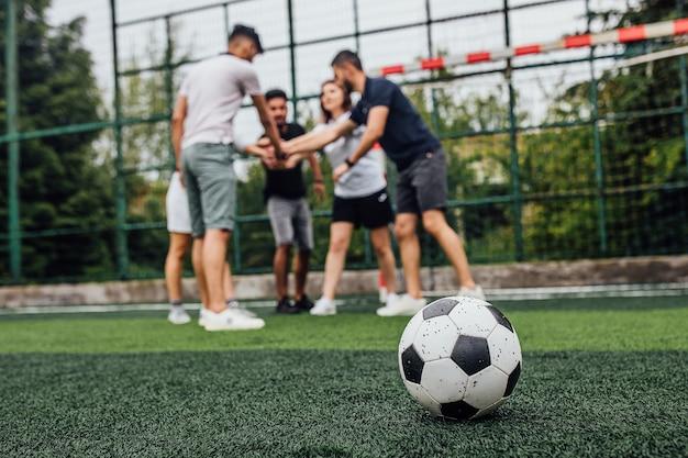 Close up van voetbal bal op groen veld... spelers gaan samen spelen...