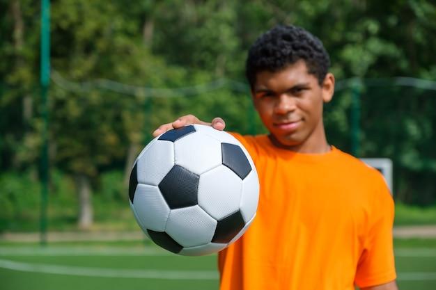Close-up van voetbal in de hand van de jonge afro-amerikaanse man. kerel die bal vasthoudt terwijl hij in de zomer buiten op het sportveld staat
