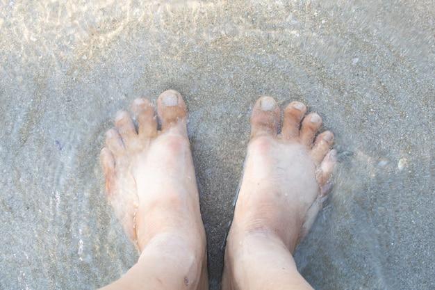 Close-up van voeten in zeewater op strand.