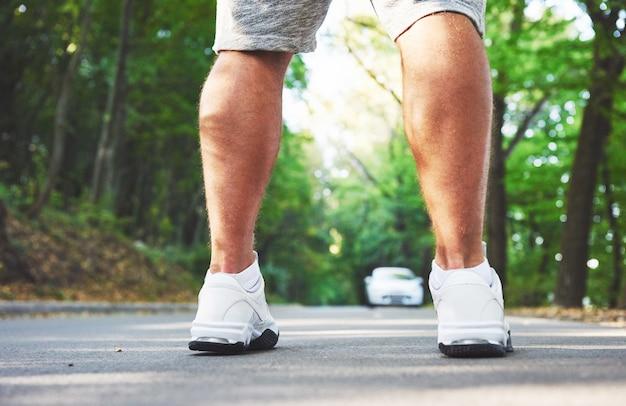 Close up van voeten van jonge atleet man loopt langs de weg in park.